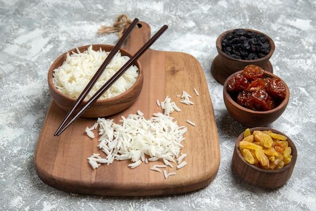 Vooraanzicht smakelijke gekookte rijst in bruine plaat met rozijnen op witruimte