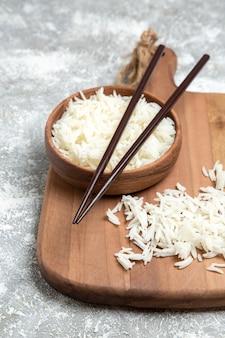 Vooraanzicht smakelijke gekookte rijst in bruine plaat met stokken op witte ruimte