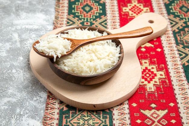Vooraanzicht smakelijke gekookte rijst in bruine plaat op witte ruimte