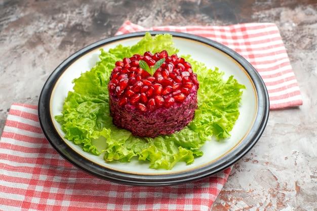 Vooraanzicht smakelijke granaatappelsalade rond gevormd op groene salade op lichte kleur voedsel gezondheid rijpe maaltijd dieet