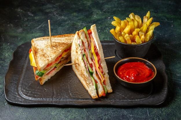 Vooraanzicht smakelijke ham sandwiches met frietjes donkere ondergrond Gratis Foto