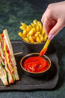 Vooraanzicht smakelijke ham sandwiches met frietjes donkere ondergrond