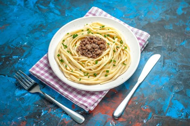 Vooraanzicht smakelijke italiaanse pasta met gehakt op blauwe kleur deeg schotel vlees maaltijd eten