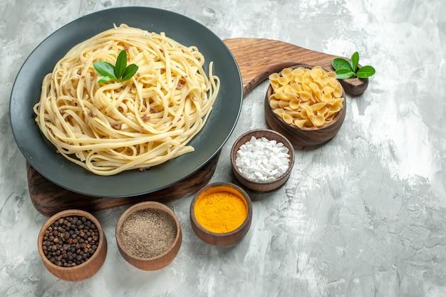 Vooraanzicht smakelijke italiaanse pasta met smaakmakers op lichte deegkleur maaltijd foto voedselschotel food