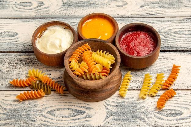 Vooraanzicht smakelijke italiaanse pasta ongebruikelijke gekookte spiraal pasta op het grijze houten bureau koken maaltijd pasta gerecht diner