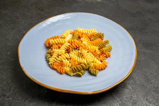 Vooraanzicht smakelijke italiaanse pasta ongebruikelijke gekookte spiraalpasta op grijze ruimte