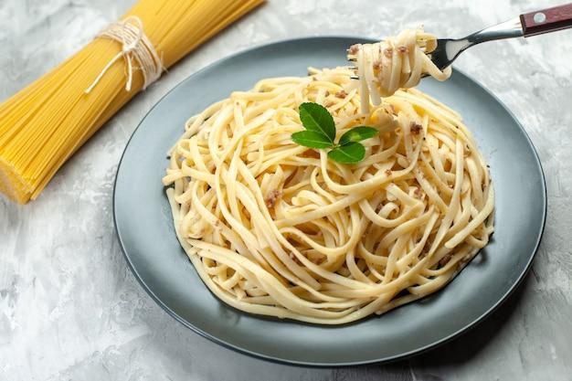 Vooraanzicht smakelijke italiaanse pasta op lichte kleur maaltijdschotel voedsel foto deeg photo