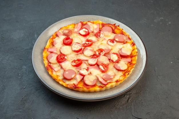 Vooraanzicht smakelijke kaaspizza met worstjes en tomaten op donkere achtergrond italiaans eten cake fastfood foto kleurdeeg
