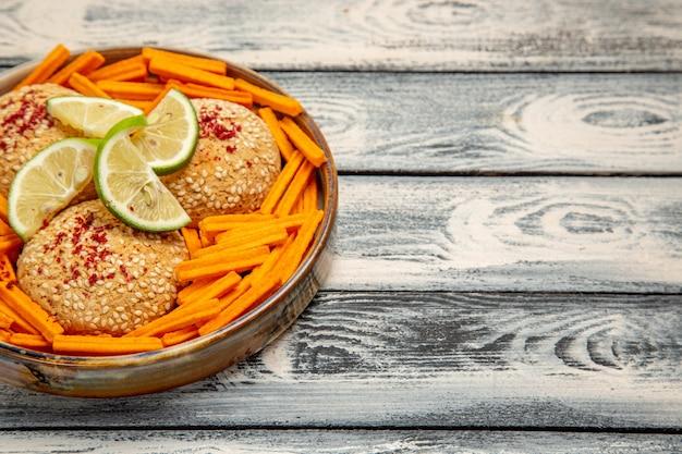 Vooraanzicht smakelijke koekjes met plakjes citroen en beschuit op het rustieke grijze bureau