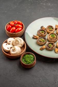 Vooraanzicht smakelijke paddenstoelenmaaltijd met verse groenten en tomaten op de donkere achtergrondschotel dinermaaltijd kokende paddestoel