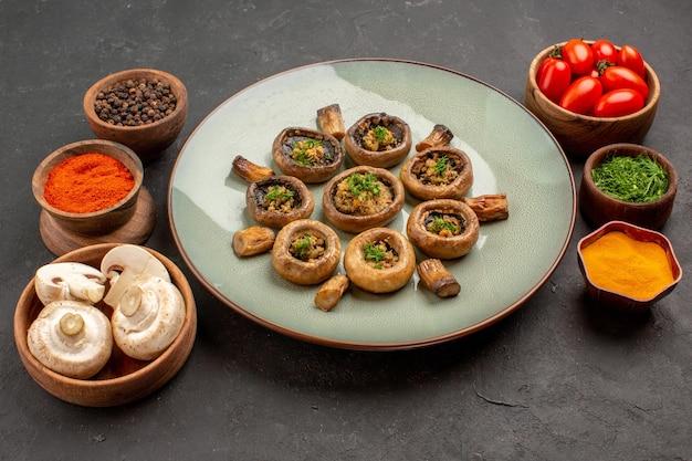 Vooraanzicht smakelijke paddenstoelenschotel met tomaten en kruiderijen op een donkere achtergrondschotelmaaltijd die paddestoeldiner kookt