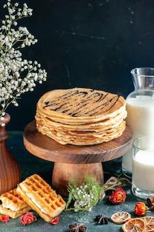 Vooraanzicht smakelijke pannenkoeken met melk op donkerblauwe ondergrond