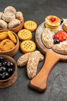 Vooraanzicht smakelijke pannenkoeken met zoete cakes en fruit op het donkere dessert van de oppervlakte zoete cake