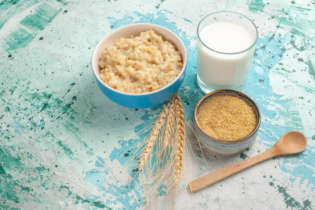 Vooraanzicht smakelijke pap met melk op de blauwe melk van het de maaltijdvoedsel van het bureauontbijt