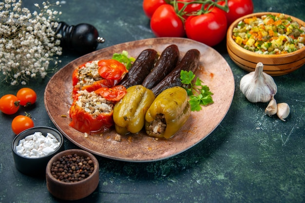 Vooraanzicht smakelijke plantaardige dolma met tomaten op blauwe achtergrond