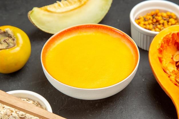 Vooraanzicht smakelijke pompoensoep binnen plaat op donkere tafel schotel kleur soep