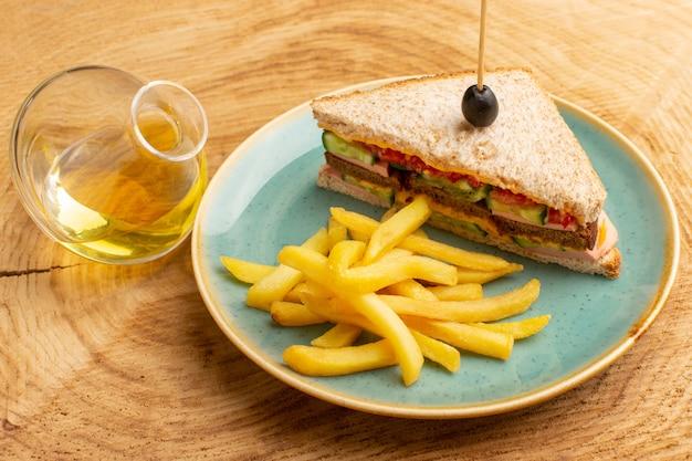 Vooraanzicht smakelijke sandwich met olijven ham tomaten groenten binnen plaat met frietjes en olie op hout