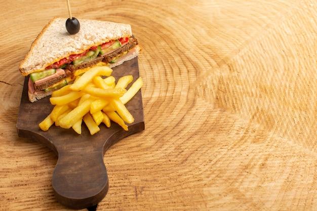 Vooraanzicht smakelijke sandwich met olijven ham tomaten groenten met frietjes op hout