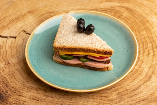 Vooraanzicht smakelijke sandwich met olijven ham tomaten groenten op hout