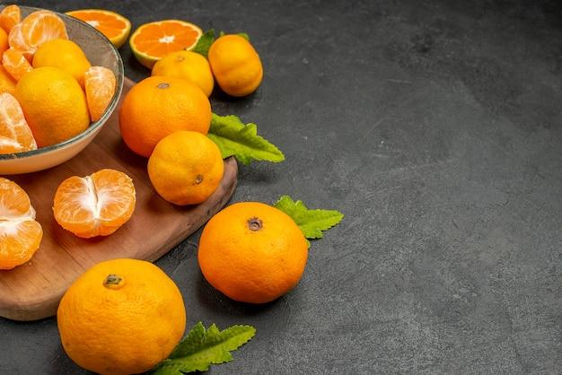 Vooraanzicht smakelijke sappige mandarijnen in plaat op donkere achtergrond, zure exotische citruskleurenfoto oranje fruit