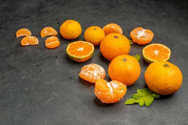 Vooraanzicht smakelijke sappige mandarijnen op donkere achtergrond exotische citrus oranje kleur foto zuur fruit