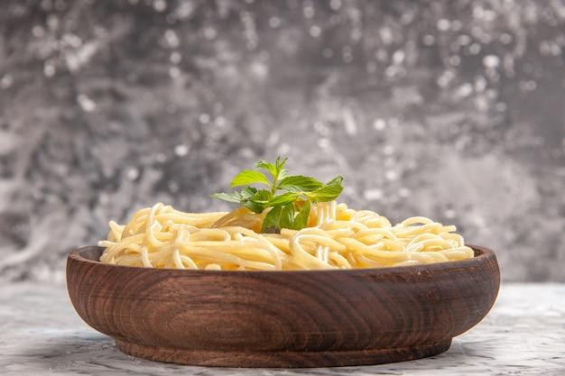Vooraanzicht smakelijke spaghetti met groen blad op lichte witte tafel maaltijdschotel deeg pasta