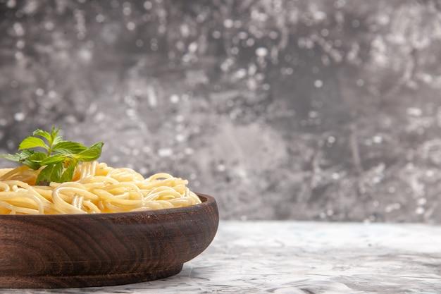 Vooraanzicht smakelijke spaghetti met groen blad op witte tafeldeeg maaltijdschotel pasta