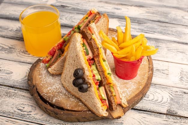 Vooraanzicht smakelijke toastsandwiches met kaasham binnen met frietsap op hout