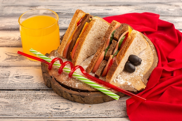 Vooraanzicht smakelijke toastsandwiches met kaasham binnen samen met sap op hout
