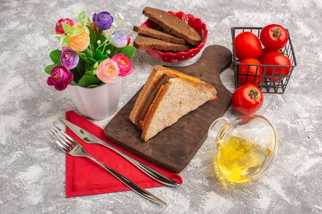 Vooraanzicht smakelijke toastsandwiches met kaasham met olietomaten en bloemen op wit