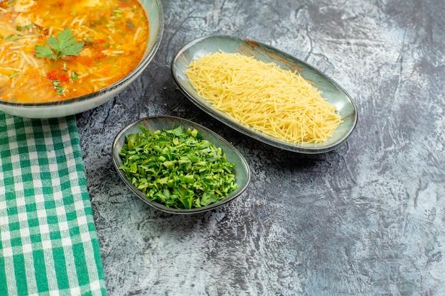 Vooraanzicht smakelijke vermicellisoep met greens en ruwe vermicelli op een lichtgrijze achtergrond warme deegwarendeeg voedselschotel saus aardappelfoto