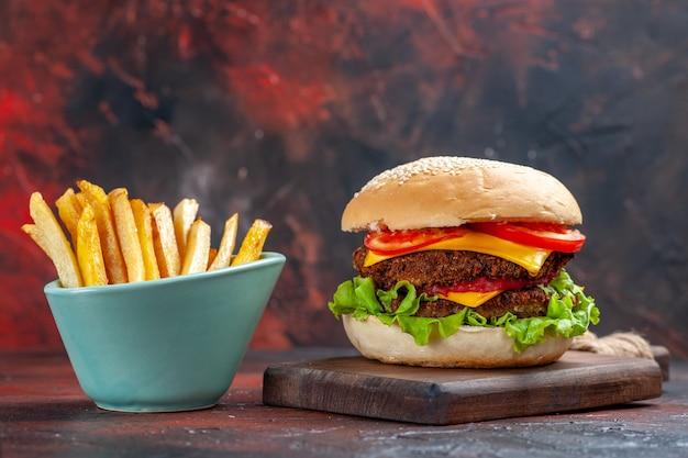 Vooraanzicht smakelijke vleesburger met frietjes op donkere achtergrond