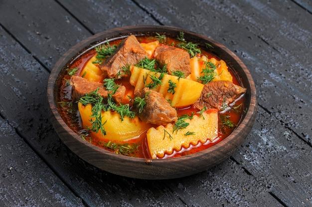 Vooraanzicht smakelijke vleessoep met aardappelen en greens op de donkere saus van de het vleesgerecht van de bureaumaaltijd