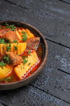 Vooraanzicht smakelijke vleessoep met aardappels en greens op een donkere schotel van de de sausmaaltijd van het bureauvlees