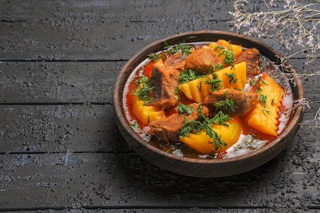 Vooraanzicht smakelijke vleessoep met greens en aardappelen op de donkere schotel van de de sausmaaltijd van het bureauvlees
