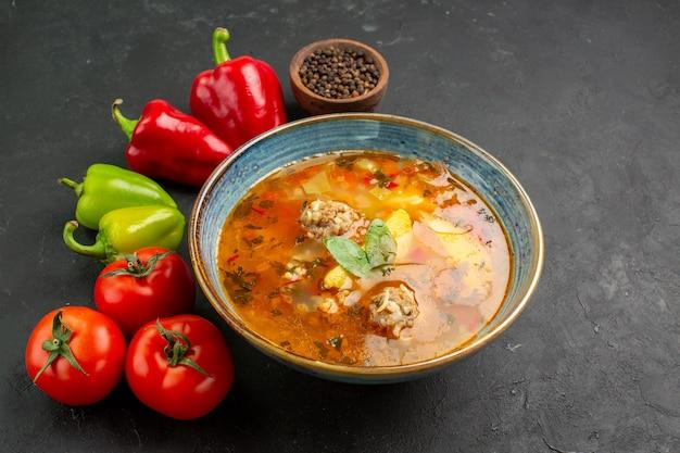 Vooraanzicht smakelijke vleessoep met verse groenten op een donkere achtergrond