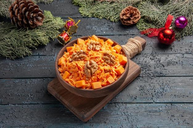 Vooraanzicht smakelijke wortelsalade met walnoten op donkerblauwe achtergrond gezondheidssalade kleur voedsel dieet noot