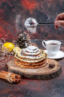 Vooraanzicht smakelijke zoete pannenkoeken met suikerpoeder op donkere achtergrond