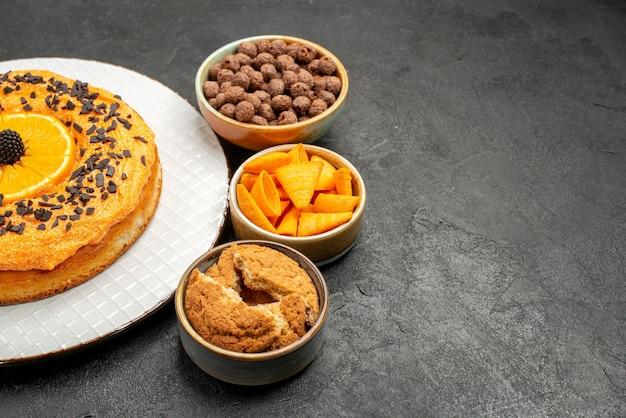 Vooraanzicht smakelijke zoete taart met stukjes sinaasappel op donkere achtergrond zoete taart dessert thee biscuit cake suiker