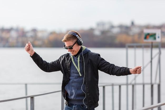 Vooraanzicht smiley blonde man muziek beluisteren en dansen