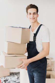 Vooraanzicht smiley jonge man met dozen