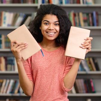 Vooraanzicht smiley meisje met twee boeken