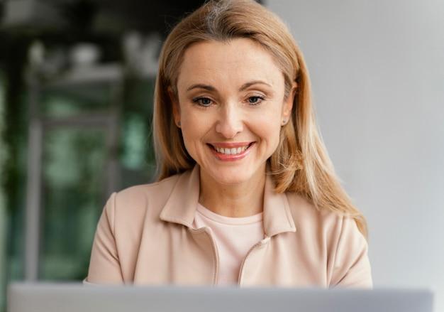 Vooraanzicht smiley vrouw die in haar kantoor werkt