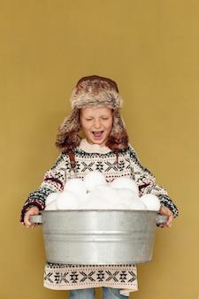 Vooraanzicht smileyjong geitje met hoed en sneeuwballen