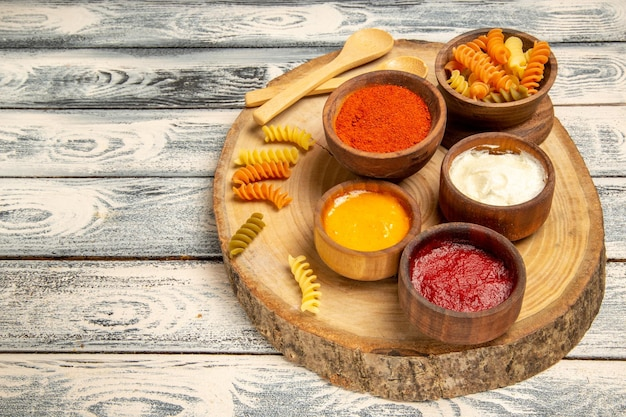 Vooraanzicht spiraal pasta met verschillende smaakmakers op grijze bureau pasta deeg kleur peper eten