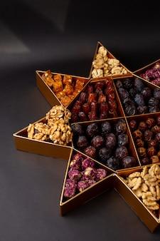 Vooraanzicht staan met verschillende noten samen met gedroogde vruchten op de donkere vloer