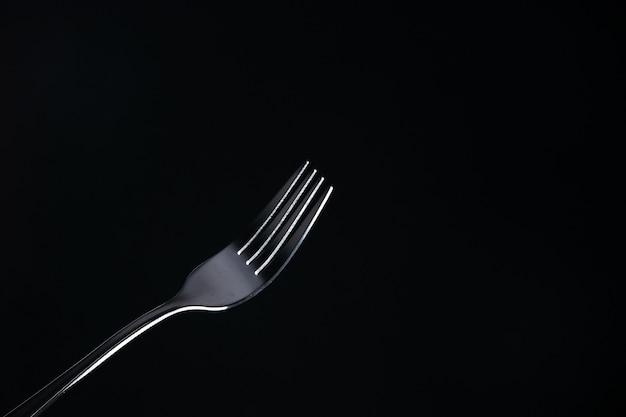 Vooraanzicht stalen vork op zwarte ondergrond met vrije ruimte