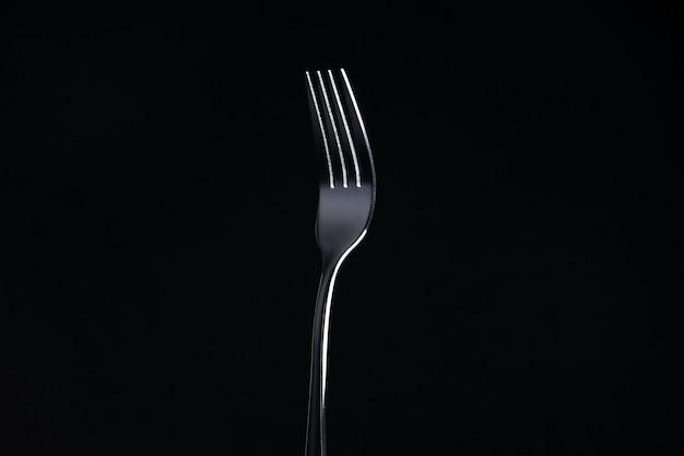 Vooraanzicht stalen vork op zwarte oppervlak vrije ruimte