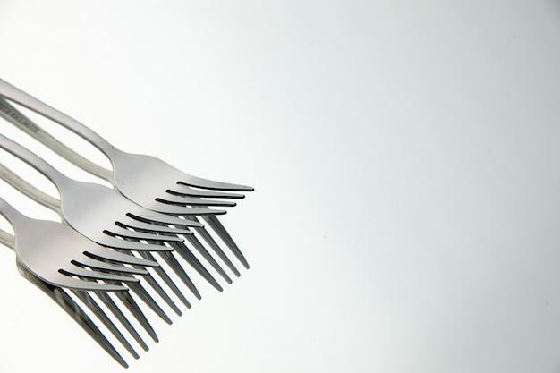 Vooraanzicht stalen vorken met reflectie in de spiegel met kopieerplaats