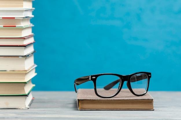 Vooraanzicht stapel boeken met een bril